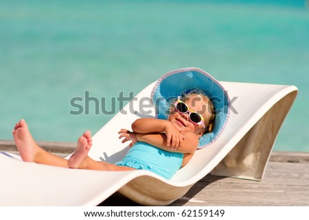 cute toddler girl in bikini, hat and sunglasses lyiing on a lounge and relaxing in tropic ocean background