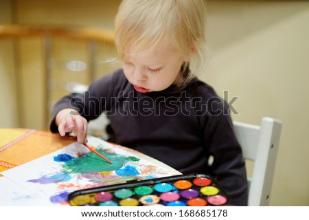 Cute toddler girl is drawing with paints in preschool