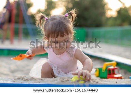 Cute toddler girl playing in sand on outdoor playground. Beautiful baby in red trousers having fun on sunny warm summer day. Child with colorful sand toys. Healthy active baby outdoors plays games #1501674440