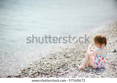 Cute toddler girl playing on pebble beach