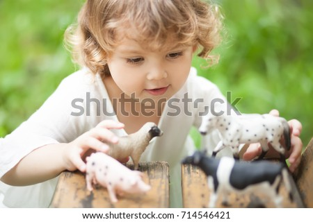 Cute toddler girl playing with farm animal figures outdoors. Summer leisure. childhood on countryside. Child learning farm animals. Early education and development #714546421