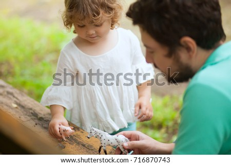 Cute toddler girl playing with her father outdoors. farm animal figures. Summer leisure. childhood on countryside. Child learning farm animals. Early education and development #716870743