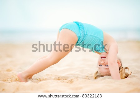 cute toddler girl practicing yoga on exotic beach