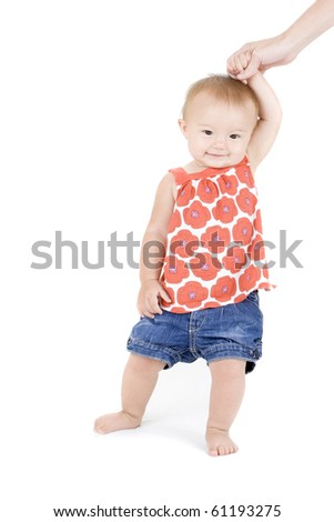 Cute toddler girl standing while mommy holds her up