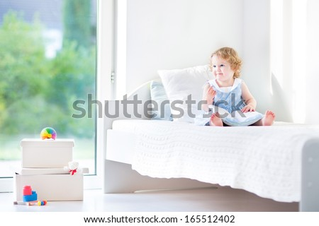 Cute toddler girl with curly hair wearing a blue dress sitting on a white bed in a sunny bedroom with big window into the garden