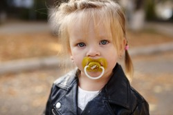 cute toddler girl with dummy on the walk