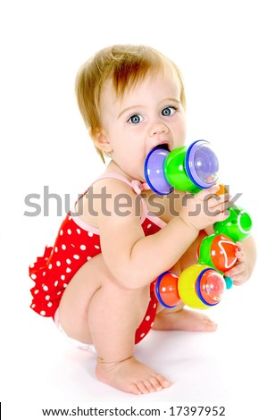 Cute toddler holding toy and chewing on it