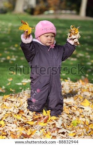 Cute toddler playing in an autumnal park
