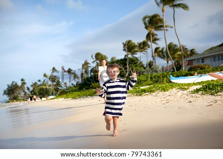 Cute toddler running away from his mother on a tropical beach
