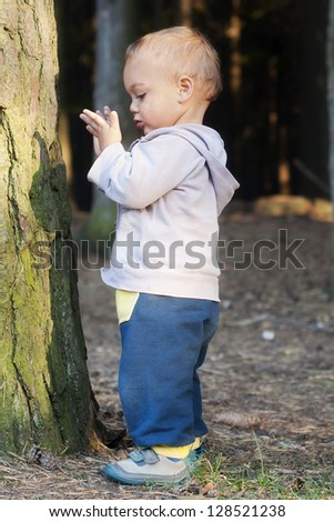 Cute toddler standing by a tree in a forest, exploring the nature.