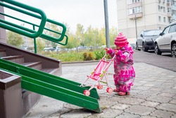cute toddler with a toy stroller walks along steel railing ramp for wheelchair, carts and strollers. gentle descent from the stairs outdoors