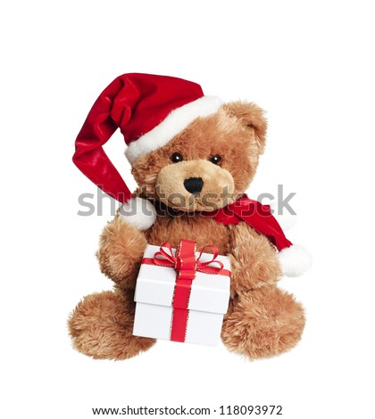 Cute toy bear with christmas gift and santa hat on white background