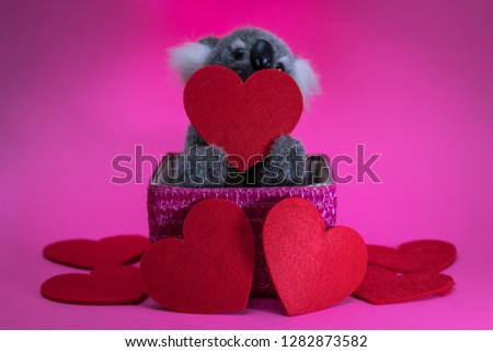 cute toy koala with red heart on pink basket. #1282873582