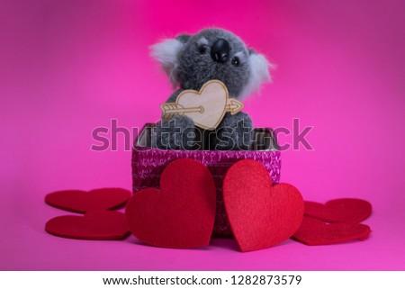 cute toy koala with wooden heart on pink basket. #1282873579