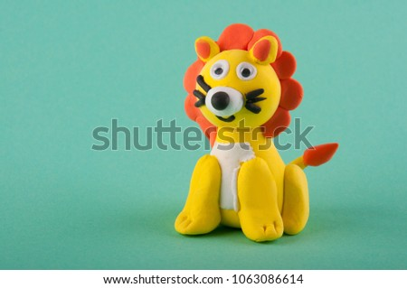 Cute toy lion made of moddeling clay sitting on green background