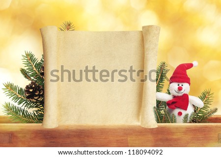 Cute toy snowman on golden background with blank scroll