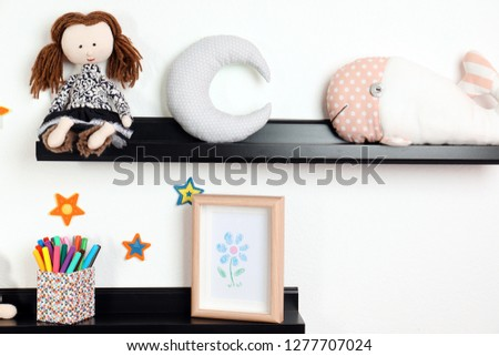 Cute toys and picture on shelves in child room