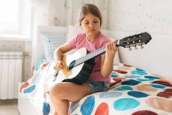 Cute tween girl in pink t-shirt play guitar sit on bed in bright room at home