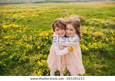 cute twin sisters, embrace on a background field with yellow flowers