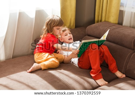 Cute two little kids, brother and sister  reading a book together sitting on a sofa at home. #1370392559