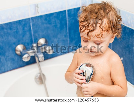 Cute two year old boy taking a relaxing bath with foam.  The symbol of purity and hygiene education.