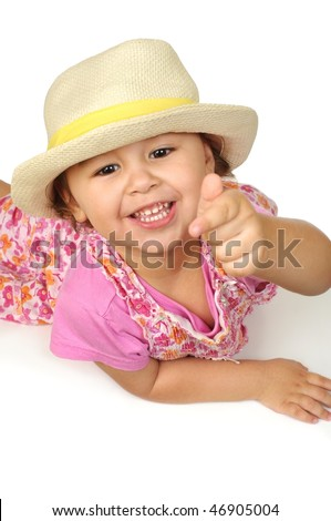 Cute two-year-old girl in a pink outfit and yellow straw hat pointing, isolated on white