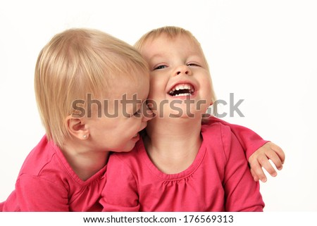 Cute two year old identical twin girls laughing