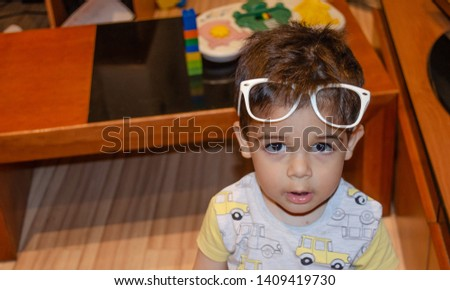 2a2aa6cf83c4 Cute two years old boy playing with white glasses and making funny faces,  blur #