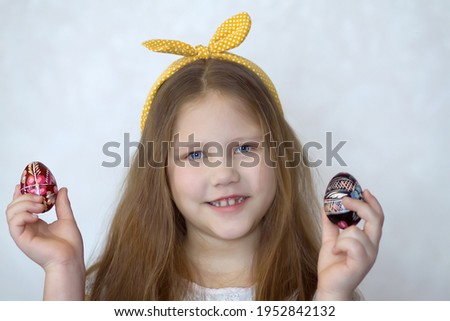 Cute ukrainian smiling girl with colored easter eggs with the traditional ukrainian slavic designs. Beautiful pysanka handmade ukrainian traditional in child's hands. Selective focus Photo stock ©