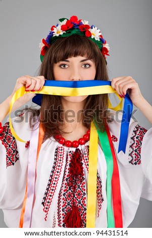 Cute Ukrainian  woman with blue yellow band on the mouth isolated on a gray background