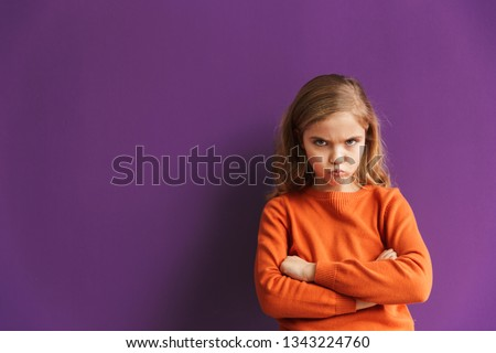 Cute upset little girl standing isolated over violet background, looking away #1343224760