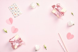 Cute Valentines day composition. Flat lay gift boxes with ribbon bow, greeting card, paper hearts, roses flowers on pastel pink background.
