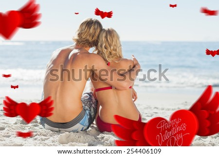 Cute valentines message against rear view of a young couple sitting on the beach