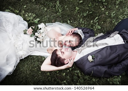 Cute Wedding couple in the outdoors arms around each other on the grass looking at each other.