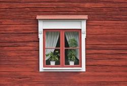 Cute window on red swedish house wall
