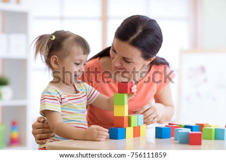 Cute woman and kid girl playing educational toys at kindergarten or nursery room #756111859