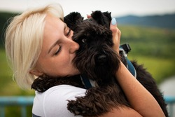 Cute woman close up portrait, hugging and kissing miniature schnauzer dog at the walk. Smiling young woman enjoying good day and posing with pet