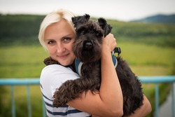 Cute woman close up portrait, hugging miniature schnauzer dog at the walk. Smiling young woman enjoying good day and posing with pet