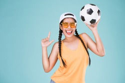 Cute woman fan of football championship. Fit girl holding ball over Blue background.