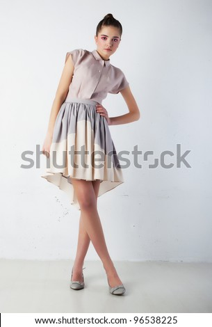 Cute Woman Fashion Model in Gorgeous Light Dress posing in studio - Sales and Shopping Concept