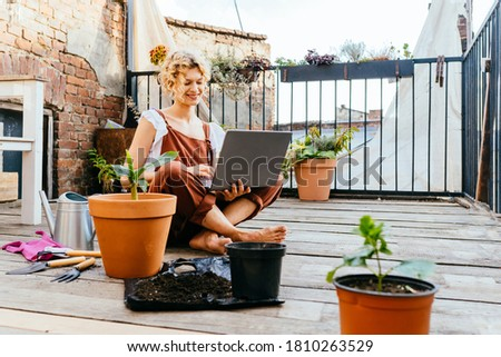 Cute woman gardener wear brown overalls, sitting on wooden floor in terrace resting, using laptop after work, smiling and speaking on video call surrounded by plants. Home gardening concept.