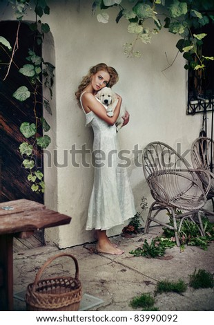 Cute woman in white dress hugging her puppy