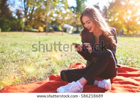 Shutterstock Cute woman is reading pleasant text message on mobile phone while sitting in the park in warm spring day,gorgeous female is listening to music  and searching information on cell telephone