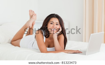 cute woman lying on bed with crossed legs and laptop looking into camera in bedroom