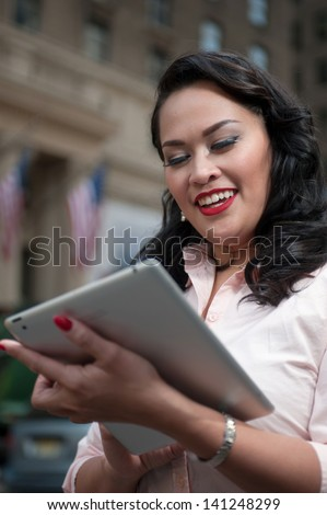 Cute woman on holiday in New York checks her tablet computer