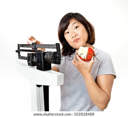 Cute woman on weight scale eating an apple and looking confused.