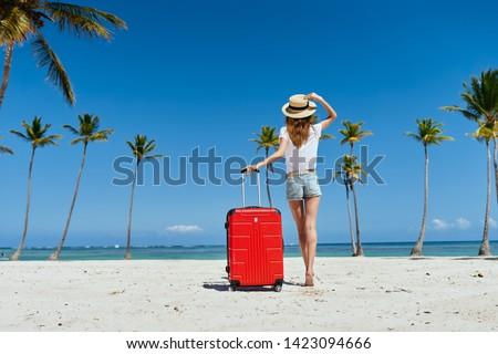 Cute woman red suitcase in a travel destination destination lifestyle luxury sand sun adventure