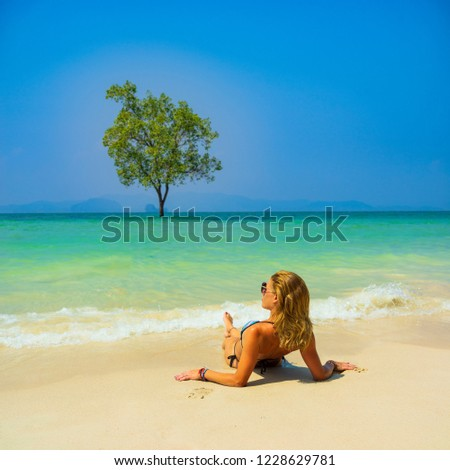Cute woman relaxing on the summer tropical beach. winter vacation in Paradise. #1228629781