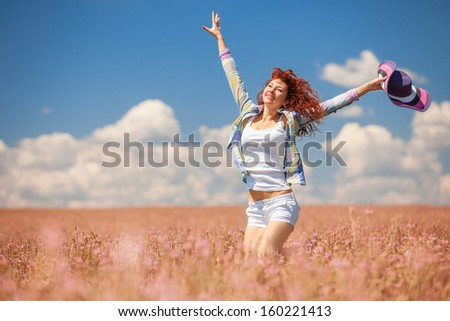 Cute woman running in the field with flowers
