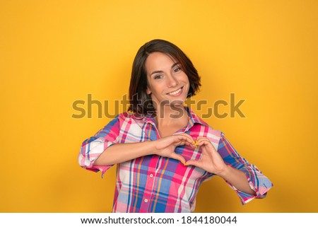 Cute woman shows heart with hands. Young smiling model wearing plaid shirt on yellow background. High quality photo Foto stock ©